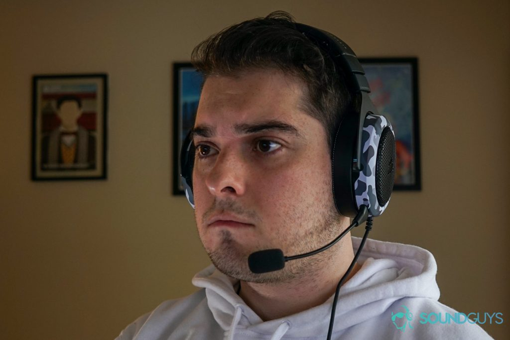 A man wears the Corsair HS60 Haptic gaming headset sitting at a desk with posters for My Brother, My Brother, and Me, and Canada Heritage Minutes in the background.