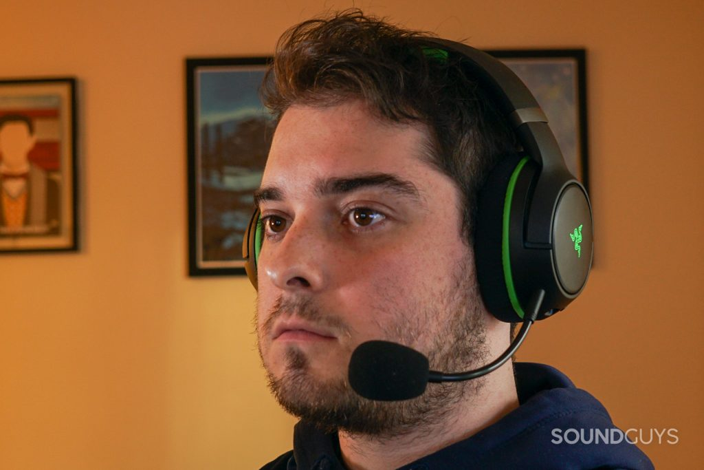 A man wears the Razer Kaira Pro gaming headset seated a PC with posters for My Brother, My Brother, and Me.