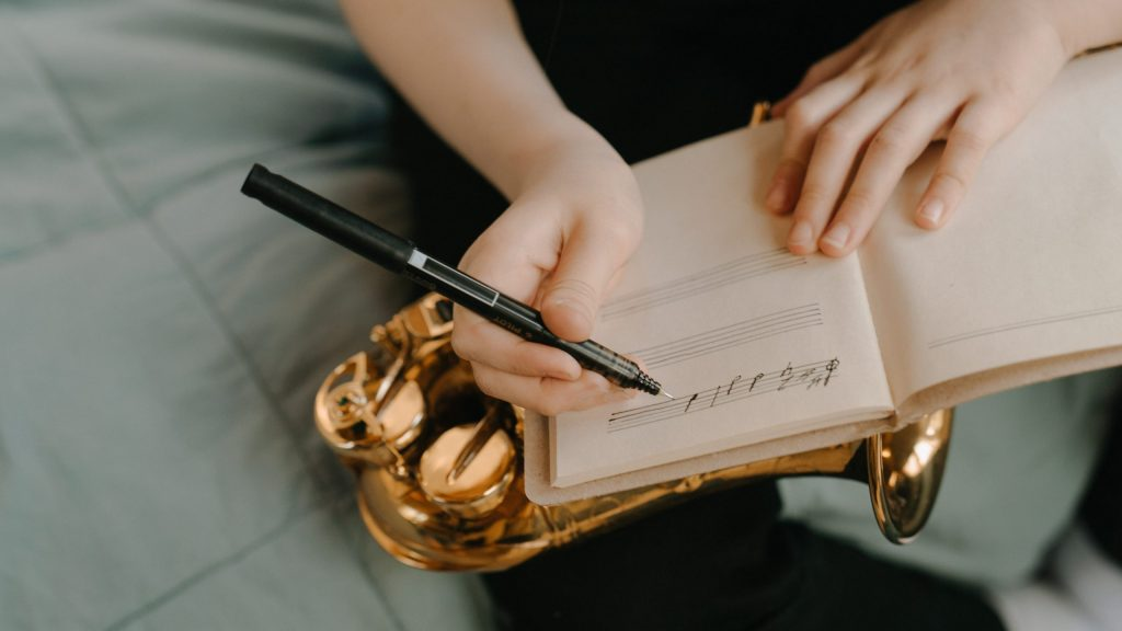 A notebook with music notation being written in it with a pen. Below the notebook is a saxophone resting on a leg. The top of a green duvet is visible.