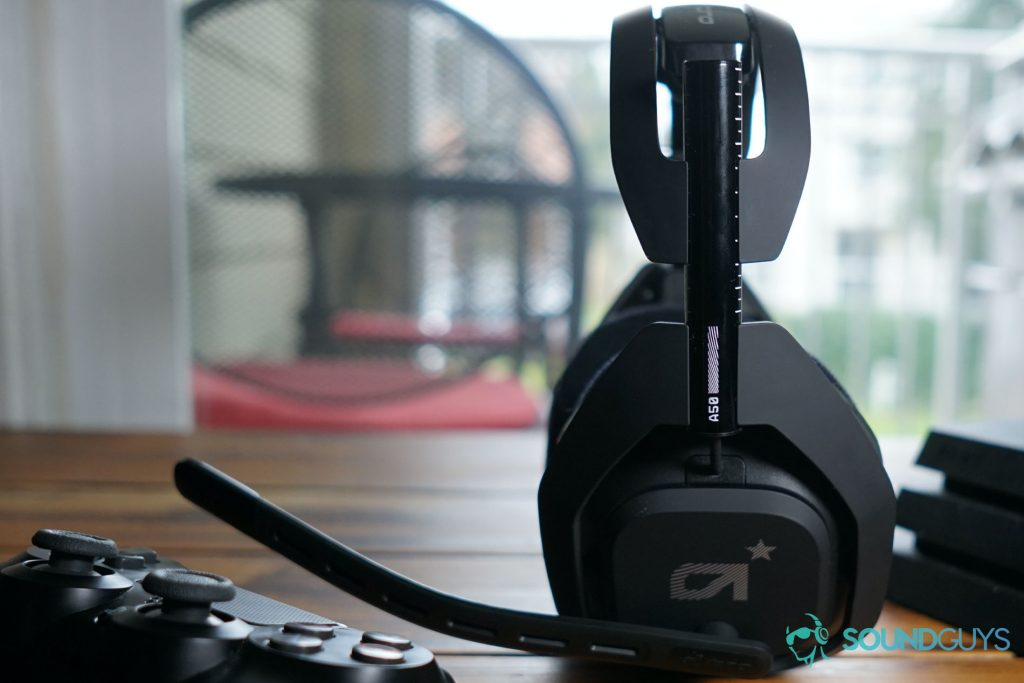 The Astro A50 Wireless sits between a dualshock controller and a Playstation 4 on a wooden coffee table.