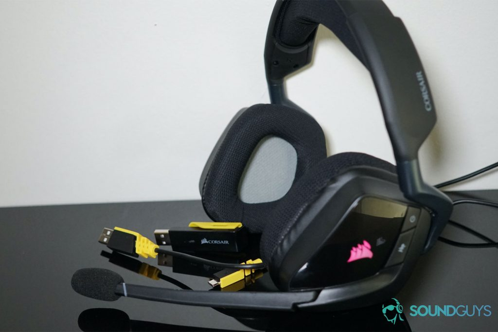 The Corsair Void RGB Elite Wireless headset sits with the cords it comes with on a black surface near a white wall.