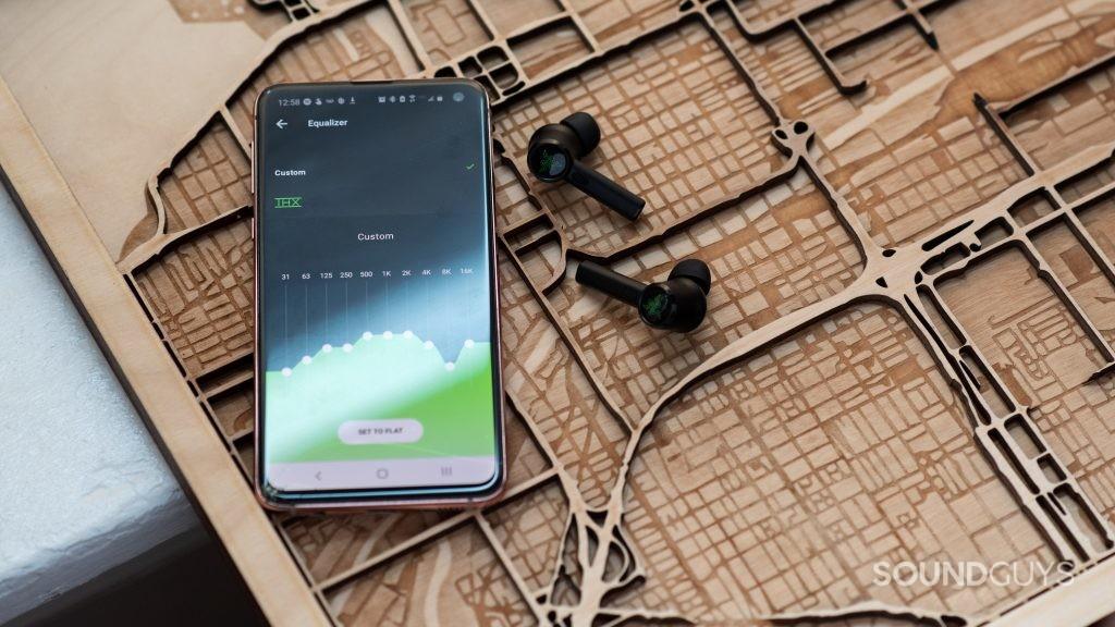 The Razer Hammerhead True Wireless Android app open on a Samsung Galaxy S10e smartphone next to the Razer Hammerhead True Wireless Pro earbuds.