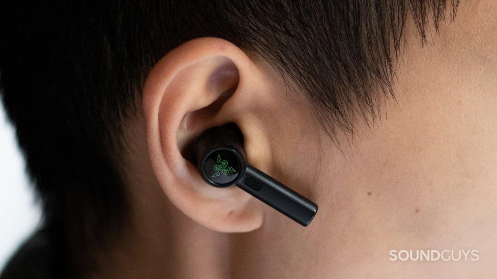 A hand holds the Razer Hammerhead True Wireless Pro noise cancelling earbuds sit in a woman's ear.
