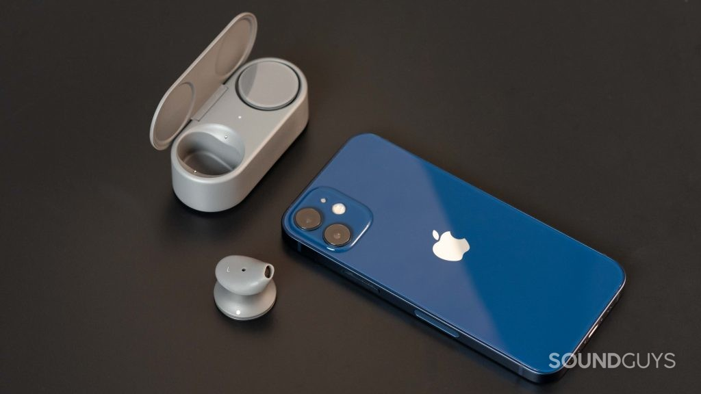 The Microsoft Surface Earbuds with one bud in the case and one outside of it next to an iPhone 12 Mini in blue.