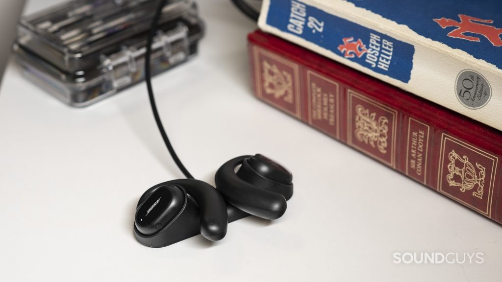 The Bose Sport Open Earbuds secured in the proprietary charging dock next to a stack of books.