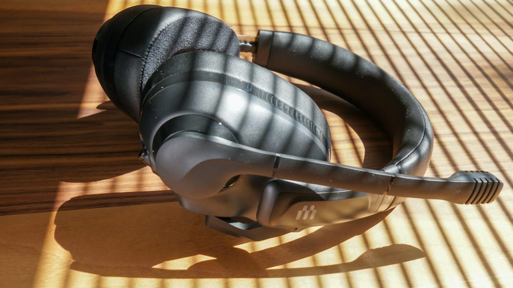 The EPOS H3 gaming headset lays on a wooden table with sunlight streaming in through drawn blinds