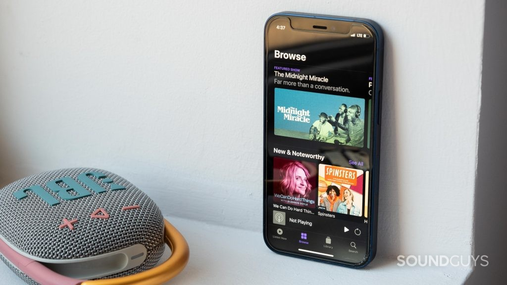An iPhone 12 Mini rests against a wall, next to the JBL Clip 4 Bluetooth speaker, and the phone displays the Apple Podcast app homepage.