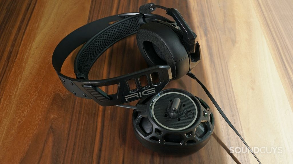 The Nacon RIG 500 Pro HC gaming headset lays on a wooden table with the right headphone detached.