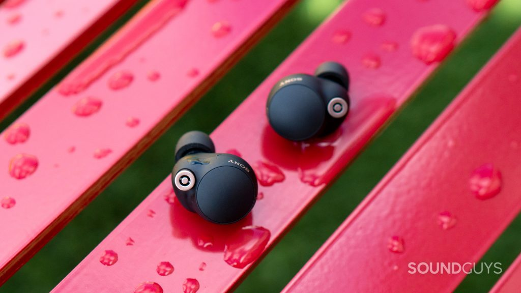 A photo of the Sony WF-1000XM4 on a wet, red bench, also with moisture on the earphones.
