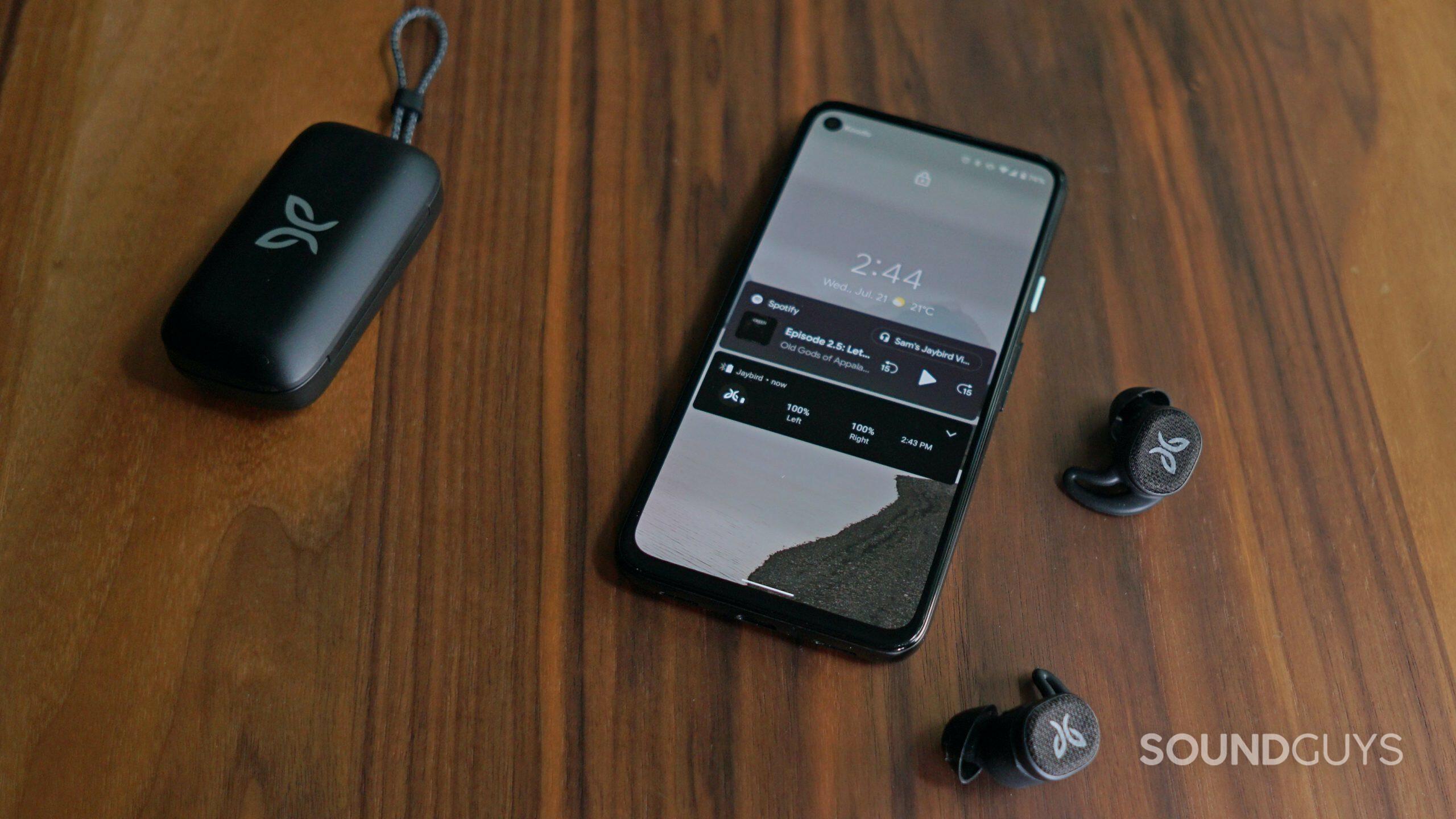 Jaybird Vista 2 earbuds and case next to smartphone.