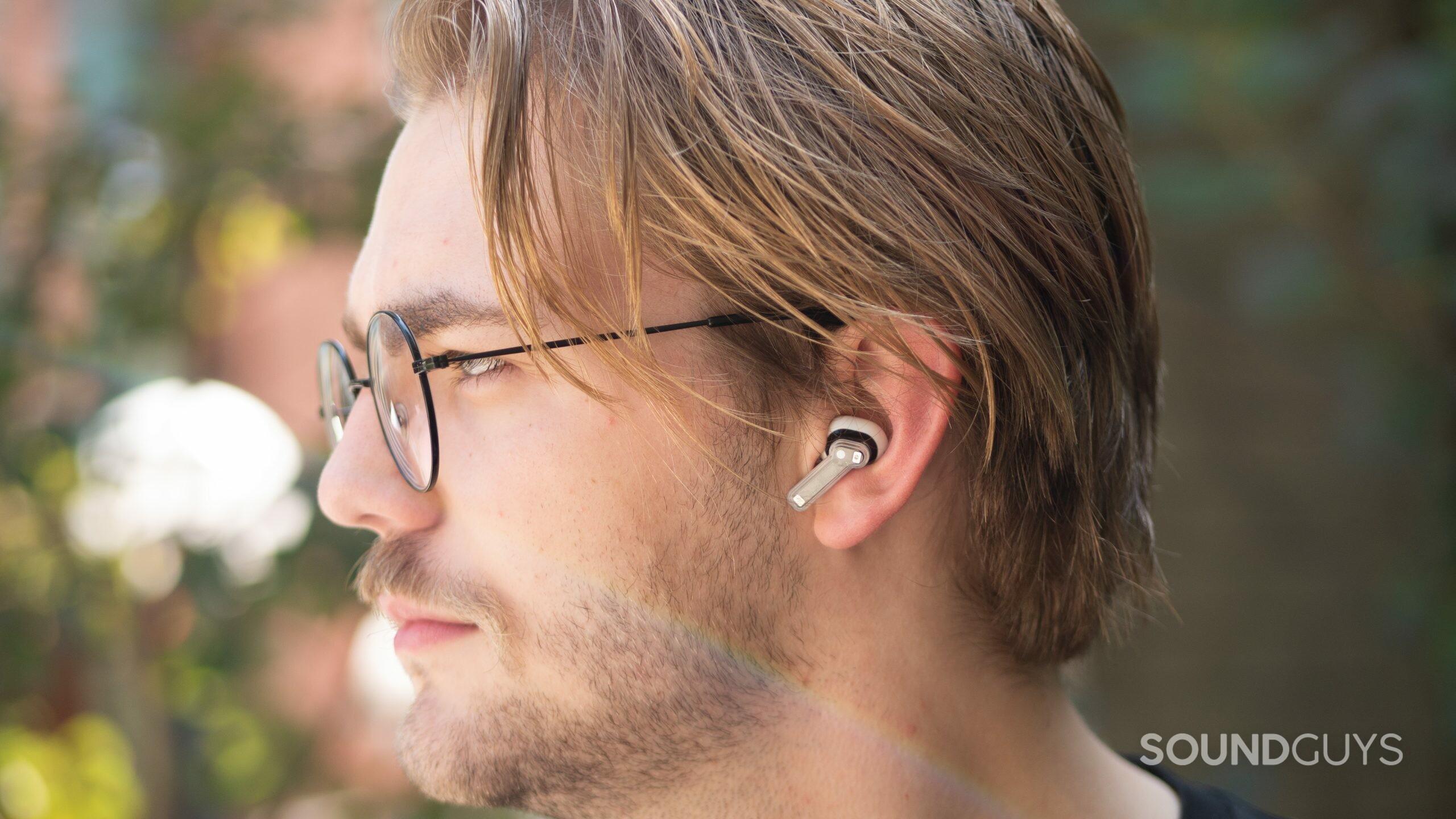 A man wears the Nothing Ear 1 noise cancelling true wireless earbuds outside.