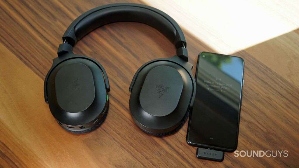 The Razer Barracuda X gaming headset lays flat on a table connected to a Google Pixel 4a via USB-C dongle.