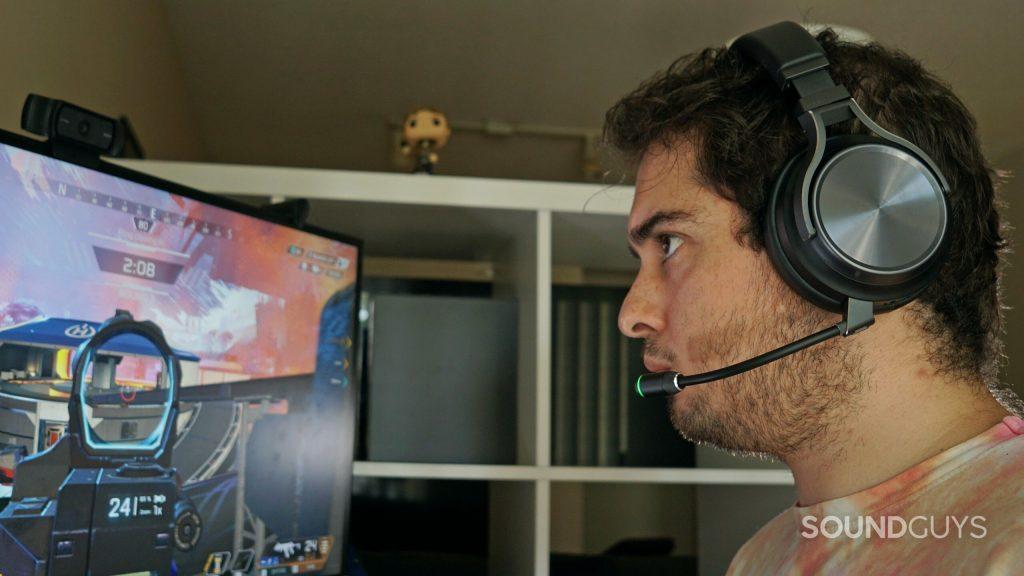 A man sits a computer playing Apex Legends wearing the Corsair Virtuoso RGB Wireless XT.