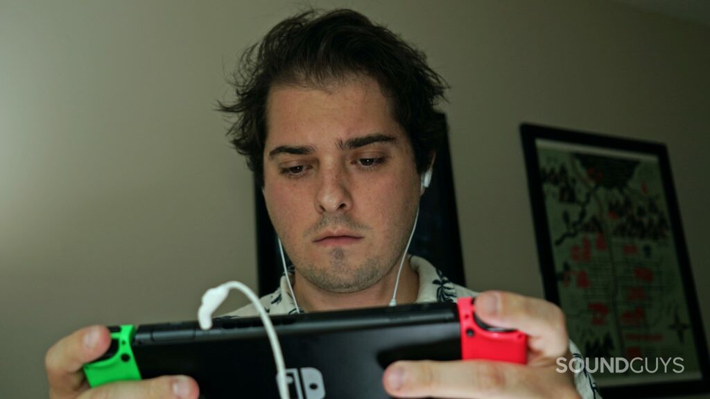 A man wears the JBL Quantum 50 while playing Nintendo Switch.
