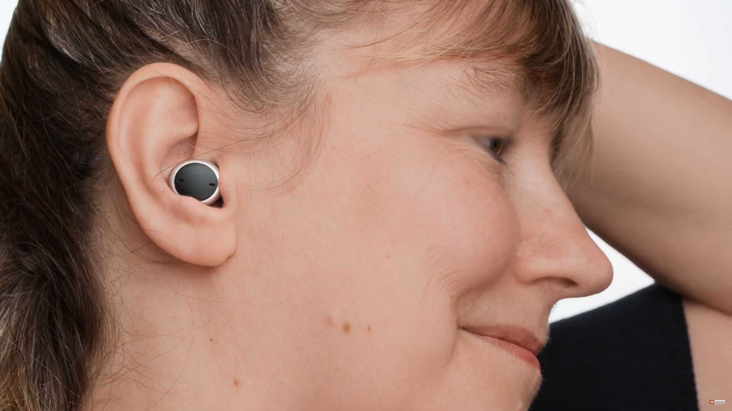 Woman inserting a Signia Active Pro hearing aid into her right ear.