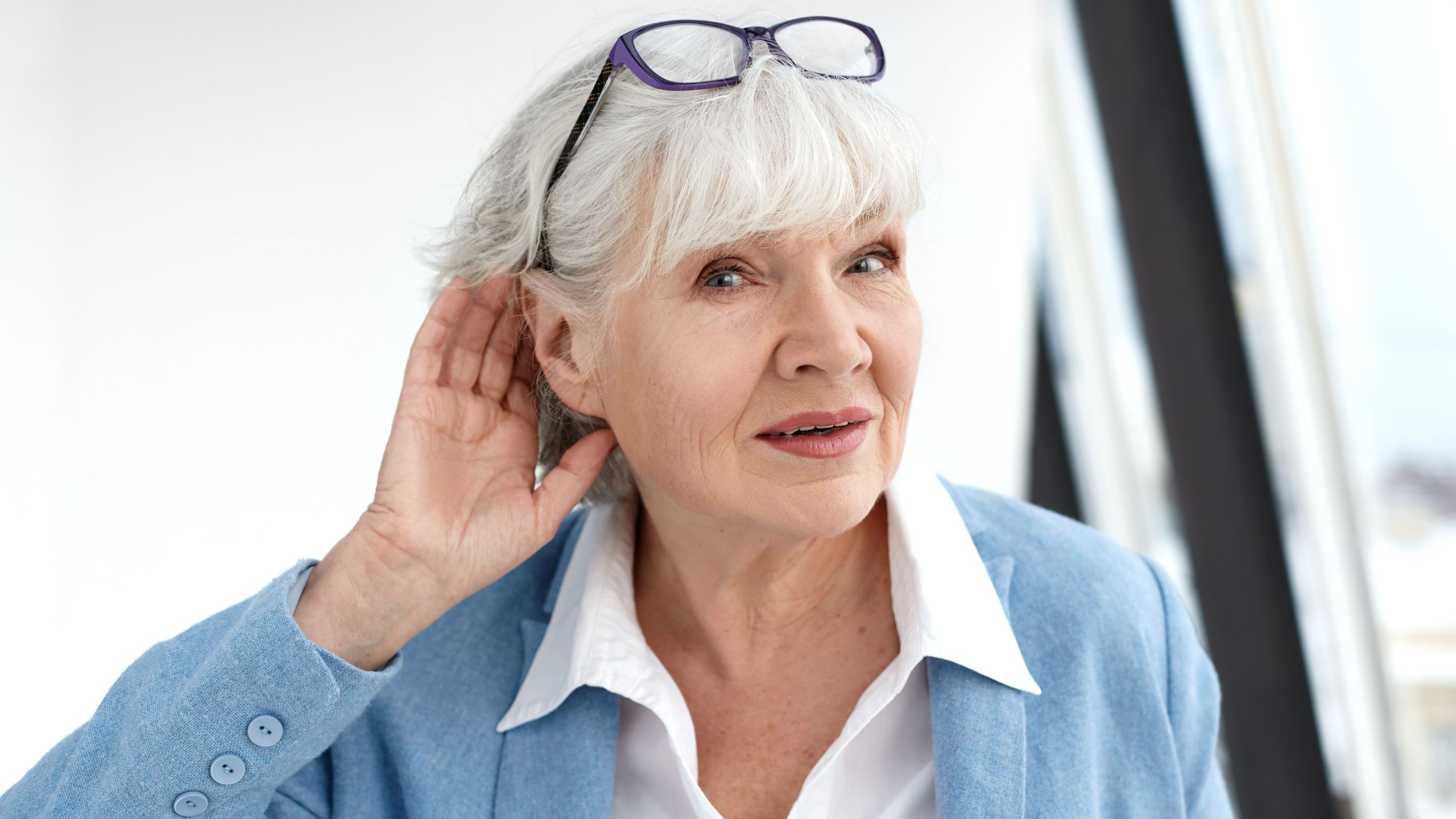 Elderly woman putting a hand behind her ear to hear better.