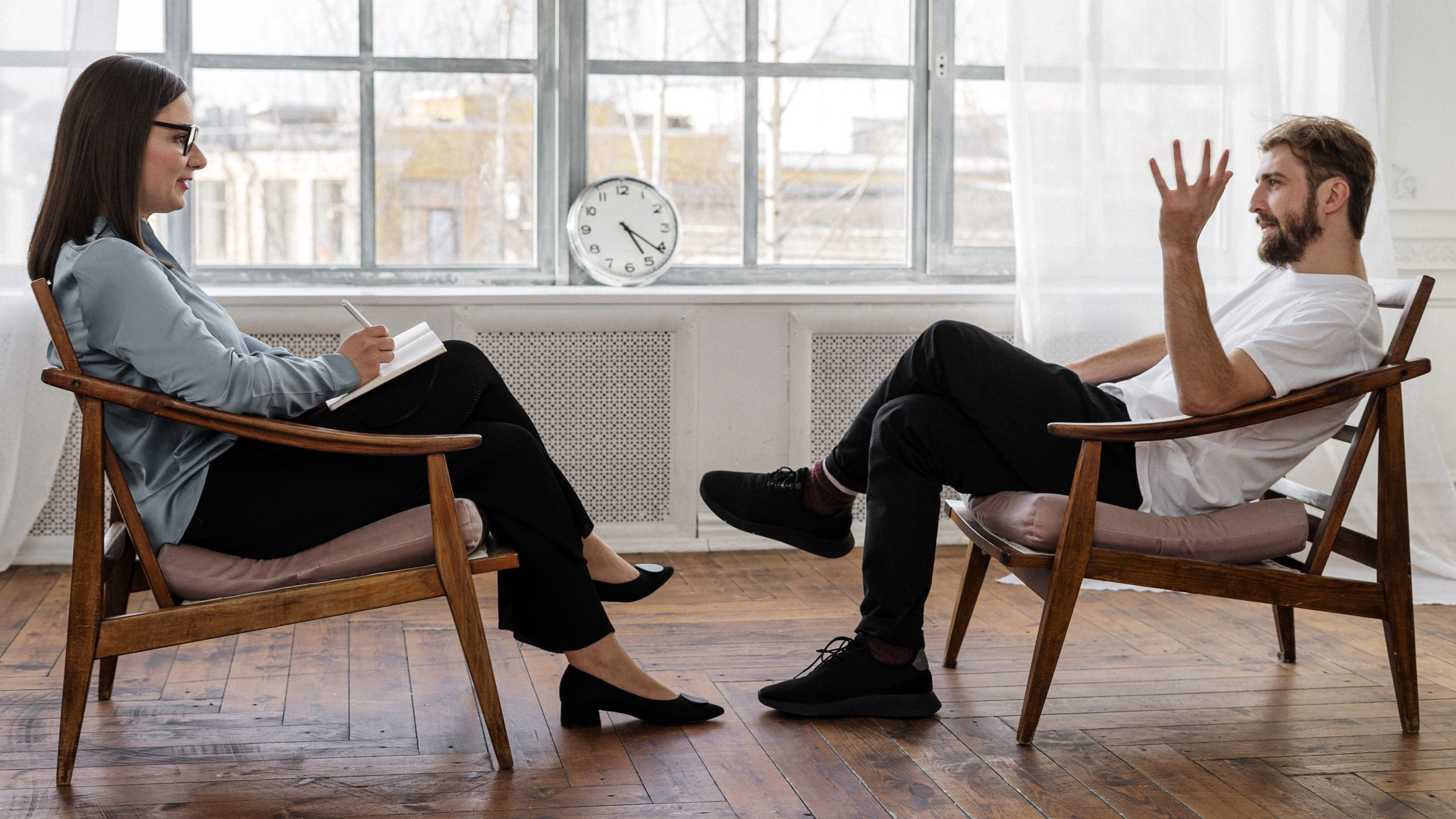 A female counselor sits across from her male patient the same way one would during tinnitus-focused therapy.