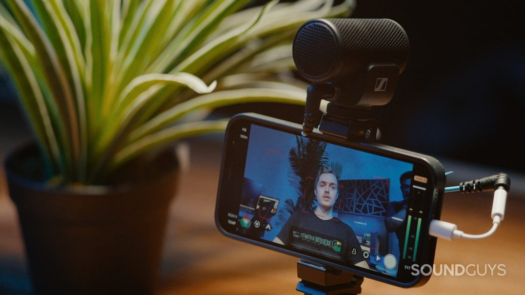 The Sennheiser MKE 200 used in a vlogging setup on an iPhone 12 as a man video chats.