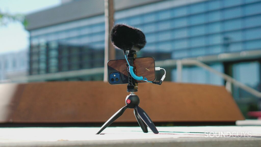 Sennheiser MKE 400 Mobile Kit mounted onto the included tripod on the ground in front of a glass building.